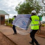 A solar panel being carried by Shinko Solar and Boreholes experienced Workers